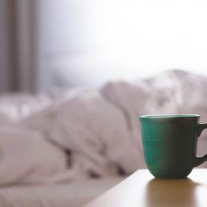 чашка с горячим напитком перед белоснежной постелью