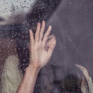 рука девушки на мокром стекле закрывает ее грустное лицо