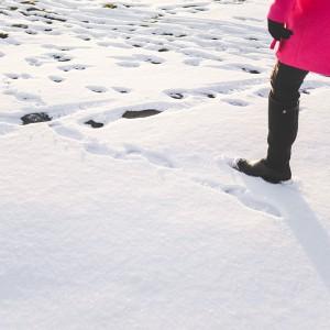 девушка в черных сапогах идет по снегу