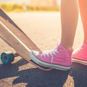 ноги девушки в розовых кедах придерживают скейт