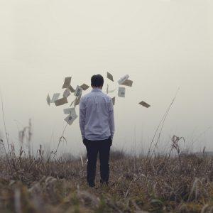 мужчина стоит в поле перед ним разлетающиеся письма