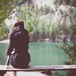 стройная девушка сидит в одиночестве на скамейке перед озером