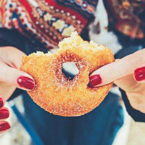 пальчики девушки держат надкусанный пончик