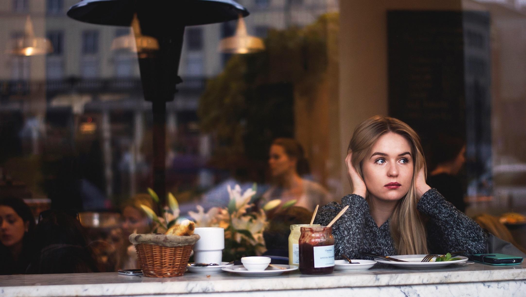 красивая девушка в кафе сидит задумчивая